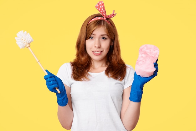 カジュアルな服装で幸せな若い女、ブラシとモップを保持し、クリーニング用品を宣伝します