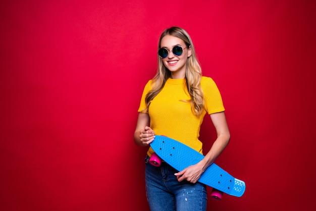赤い壁に肩にスケートボードを運ぶカジュアルな服装と帽子の幸せな若い女性