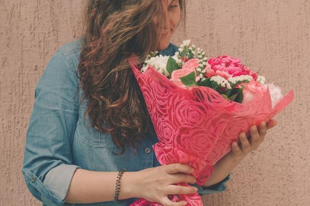 Счастливая молодая женщина в джинсовом платье с букетом нежных свежих цветов