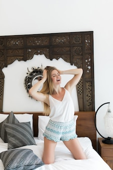 이어폰에 행복 한 젊은 여자는 침대에서 춤과 미소, 스마트 폰으로 음악을 듣고있다
