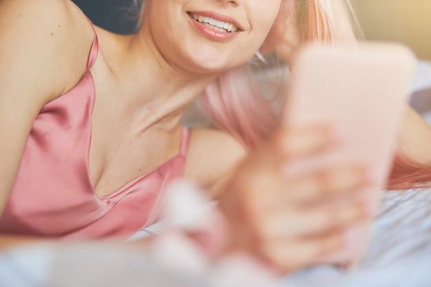 우아한 분홍색 새틴 상의를 입은 행복한 젊은 여성이 편안한 침대에 전화기를 들고 있습니다