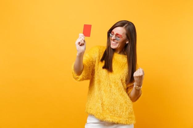 明るい黄色の背景で隔離のクレジットカードを保持している勝者のように拳を握り締める毛皮のセーターとハートの眼鏡で幸せな若い女性。人々の誠実な感情、ライフスタイルのコンセプト。広告エリア。