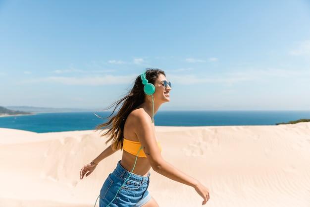 Счастливая молодая женщина в наушниках на берегу моря