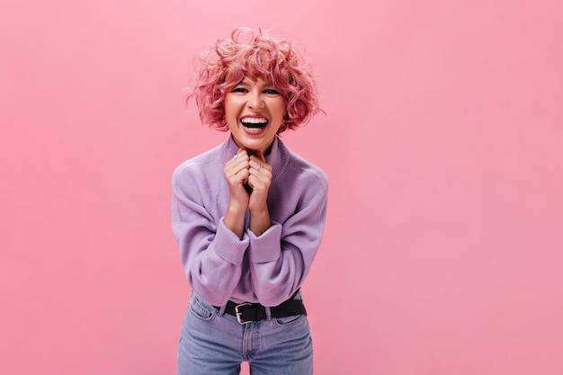 분홍색 벽에 웃고 있는 청바지와 보라색 스웨터를 입은 행복한 젊은 여성