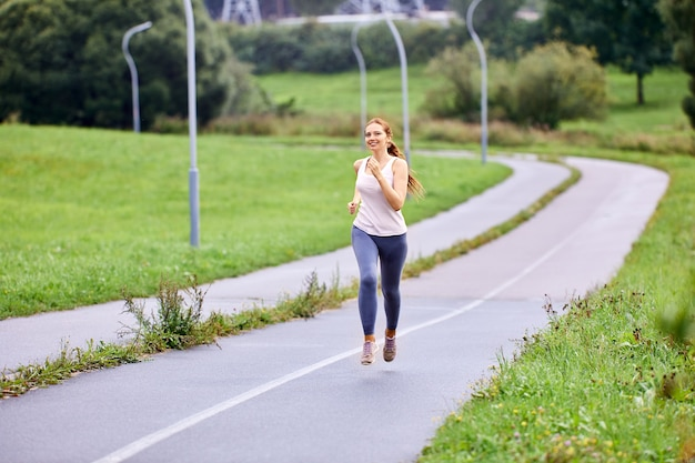 Счастливая молодая женщина в леггинсах бежит в городском саду