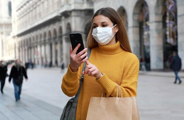 Счастливая молодая женщина в защитной маске, держащая хозяйственные сумки с помощью смартфона на городской улице