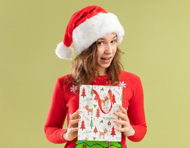 赤いクリスマスセーターとサンタ帽子の幸せな若い女性は、緑の背景の上に元気に立って笑顔のクリスマスプレゼントと紙袋を保持しています