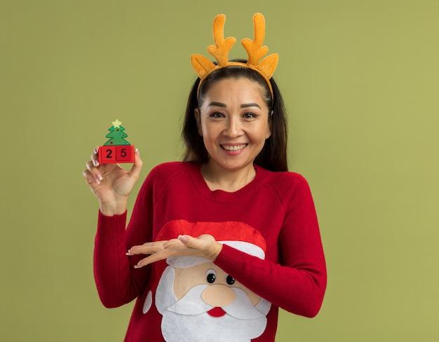 鹿の角と面白い縁を身に着けている赤いクリスマスセーターの幸せな若い女性は、緑の壁の上に元気に立って笑顔で日付25の腕のおもちゃの立方体を提示します