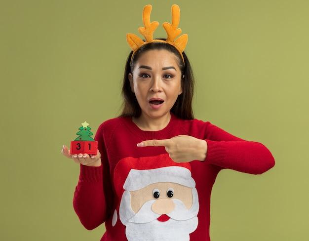 鹿の角で面白いリムを身に着けている赤いクリスマスセーターの幸せな若い女性は、緑の背景の上に立っているキューブを人差し指で指して驚いて見える新年の日付のおもちゃのキューブを示しています