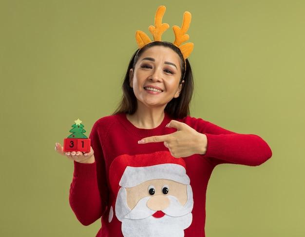 녹색 배경 위에 서있는 큐브에서 검지 손가락으로 유쾌하게 가리키는 새 해 날짜와 장난감 큐브를 보여주는 사슴 뿔을 가진 재미있는 테두리를 입고 빨간 크리스마스 스웨터에 행복 한 젊은 여자