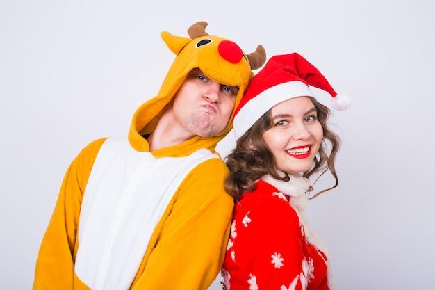 Счастливая молодая женщина в шляпе санта-клауса и мужчина в карнавальном костюме оленя.