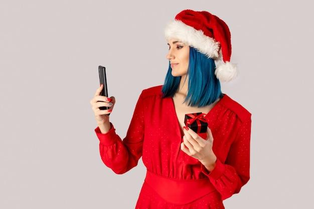회색 배경 위에 선물 상자와 스마트 폰 산타 모자에 행복 한 젊은 여자. 크리스마스 온라인 쇼핑 판매 개념