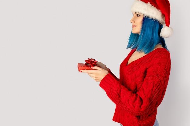 Счастливая молодая женщина в шляпе санта с подарочной коробкой. рождественские покупки продажа концепция