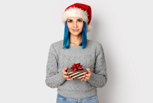 회색 배경 위에 선물 상자 산타 모자에 행복 한 젊은 여자. 크리스마스 쇼핑 판매 개념