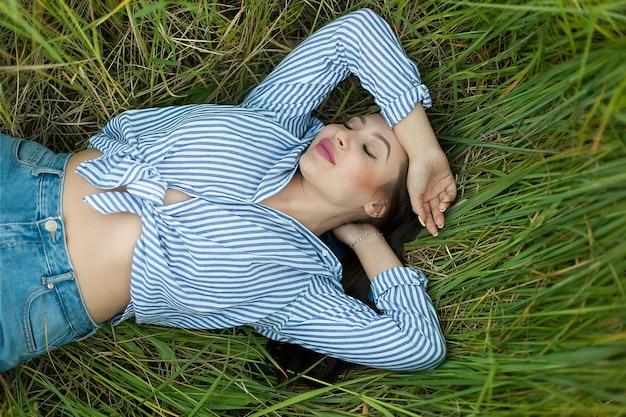 Счастливая молодая женщина в стильной одежде лежит на зеленой красивой лужайке, смотрит в камеру и улыбается