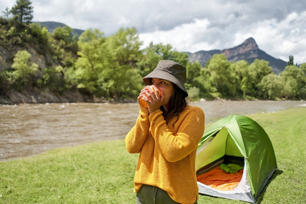 산 모험에서 따뜻한 차 또는 커피 캠핑을 마시는 텐트에서 행복한 젊은 여성