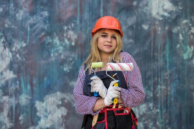色の壁の近くにペイントローラーを保持している制服を着た幸せな若い女性。家の装飾の概念