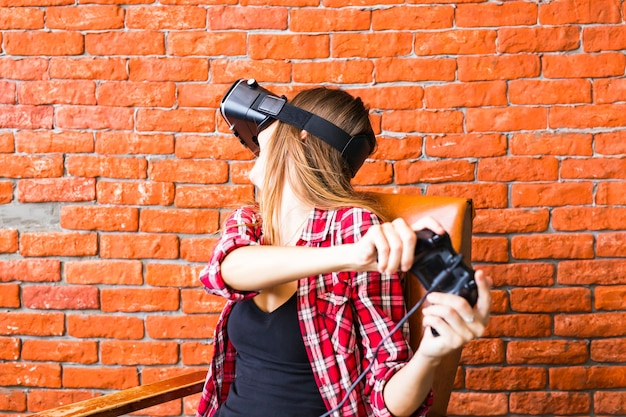 가상 현실 헤드셋 또는 3d 안경 및 집에서 컨트롤러 게임 패드로 비디오 게임을하는 헤드폰에 행복 한 젊은 여자