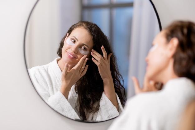 Счастливая молодая женщина в белом халате стоит перед зеркалом в ванной и накладывает на лицо патчи под глазами