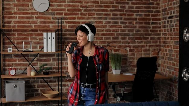白いヘッドフォンで幸せな若い女性は、スマートフォンでお気に入りの音楽を聴いて楽しんでいます。