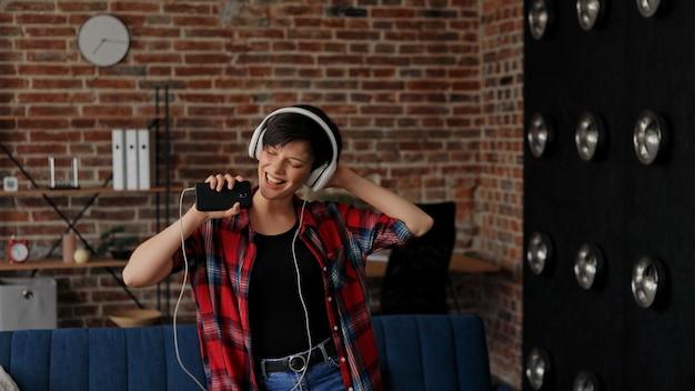 白いヘッドフォンで幸せな若い女性は、スマートフォンでお気に入りの音楽を聴いて楽しんでいます。 Premium写真