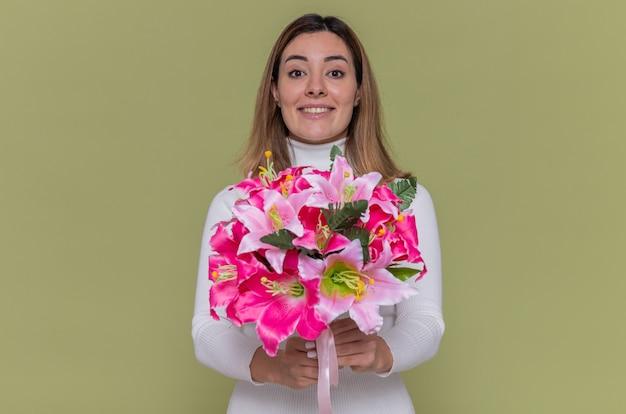 Счастливая молодая женщина в белой водолазке держит букет цветов, глядя вперед, весело улыбаясь, празднует международный женский день, стоя над зеленой стеной