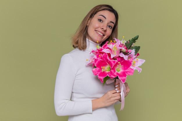 緑の壁の上に立って国際女性の日を祝って元気に笑顔の正面を見て花の花束を保持している白いタートルネックの幸せな若い女性