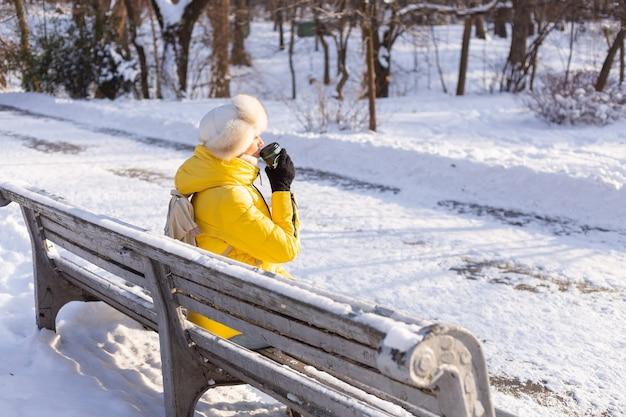 Счастливая молодая женщина зимой в теплой одежде в заснеженном парке в солнечный день сидит на скамейках и наслаждается свежим воздухом и кофе в одиночестве