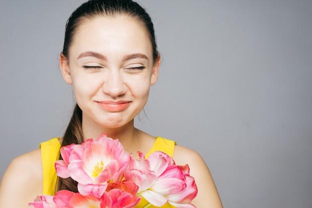 노란 드레스를 입은 행복한 젊은 여성은 향기로운 분홍색 봄 꽃과 미소의 큰 꽃다발을 들고