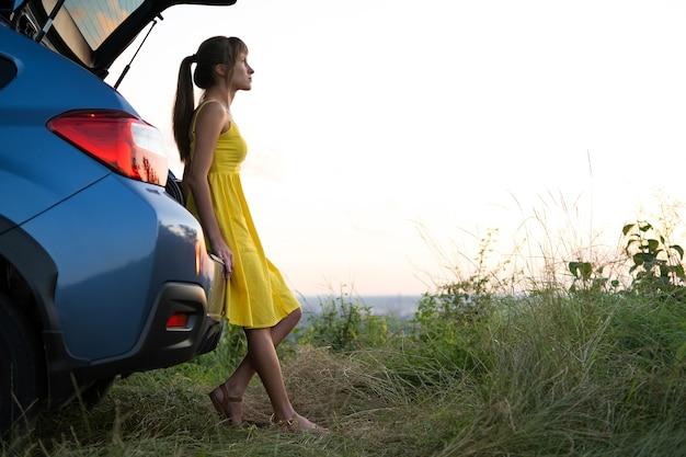 夏の自然の夕日の景色を見ている彼女の車の近くに立っている黄色のドレスを着た幸せな若い女性。旅行と休暇のコンセプト。