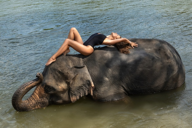 Happy young woman is bathing with the elephant in the river