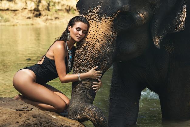 幸せな若い女性が川で象と一緒に入浴しています