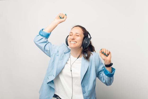 幸せな若い女性が踊り、ヘッドフォンで音楽を聴いています。