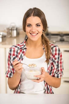 Happy young woman is eating muesli in a kitchen.