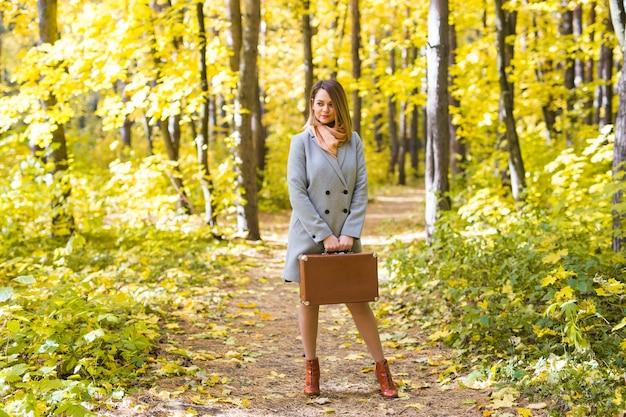 행복 한 젊은 여자는 숲에 복고풍 가방으로 여행을가는