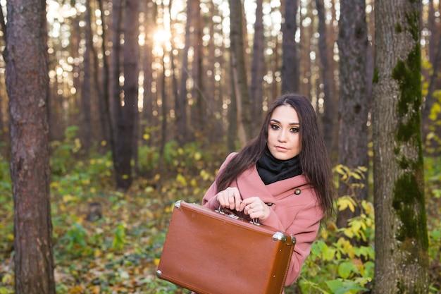 행복 한 젊은 여자는 복고풍 가방 여행에가