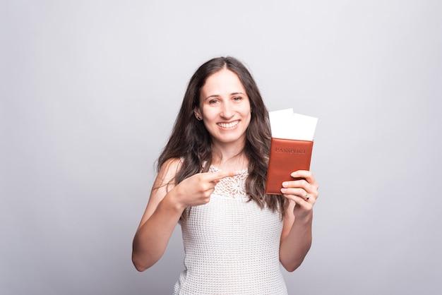 Счастливая молодая женщина держит паспорт и с некоторыми билетами улыбается и смотрит в камеру возле серой стены