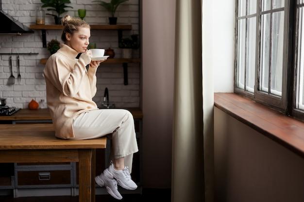 Счастливая молодая женщина находится в уютной домашней атмосфере, сидит за кухонным столом и держит в руках чашку кофе. фото высокого качества