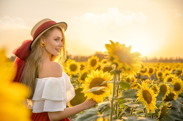 幸せな若い女は日没時のひまわり畑に