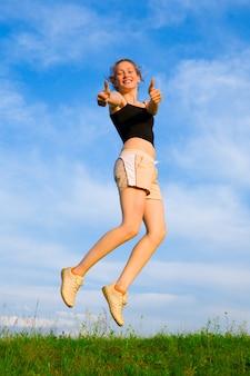 Счастливая молодая женщина прыгает на зеленой траве под небом