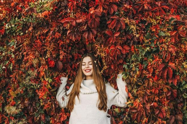 행복 한 젊은 여자는 빨간 담쟁이의 큰 벽에 누워있다.
