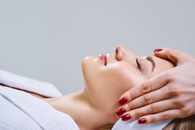 幸せな若い女性は、顔の専門家が彼女の肌で作業している間、ソファに横たわっています