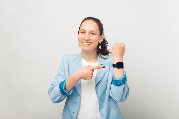 행복한 젊은 여성이 그녀가 차고 있는 손목시계를 가리키고 있습니다.