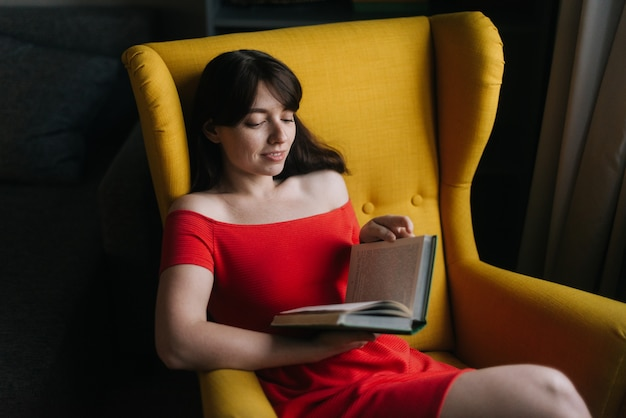 Happy young woman is reading a book in a yellow soft chair