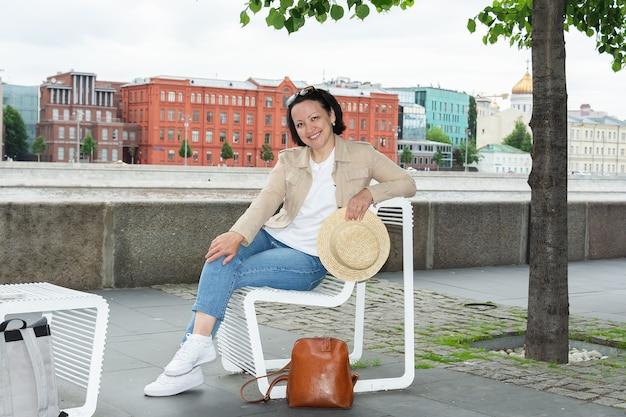 幸せな若い女性は夏にモスクワ川の堤防のベンチで休んで、笑っています。