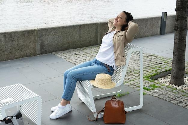 幸せな若い女性は、夏に川の堤防のベンチで休んで、笑っています。