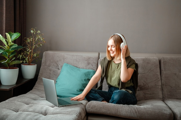 幸せな若い女は、ヘッドフォンのラップトップでソファに座っています。リモートワーク、オンライン学習、オンラインショッピング。リビング ルームのホーム インテリアで休む。自宅からの会議でビデオ通話で話している女性。