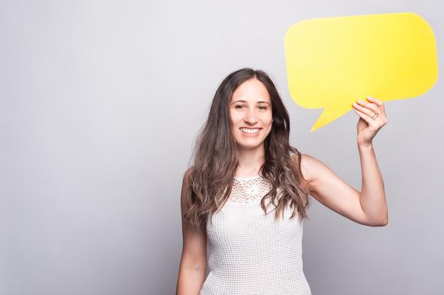 Счастливая молодая женщина улыбается в камеру и держит желтый пустой речевой пузырь