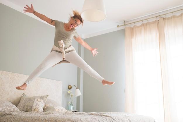 幸せな若い女が朝起きてベッドに飛び乗って笑っている