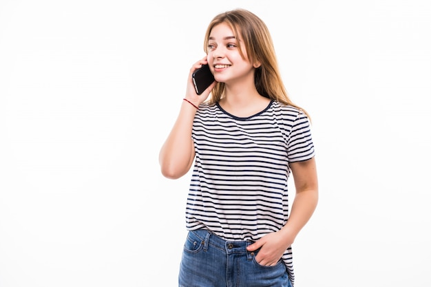 Happy young woman is talking by phone on white wall.